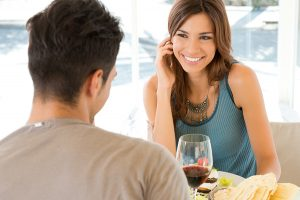Young Woman In Restaurant Having Meal And Wine With Her Boyfriend